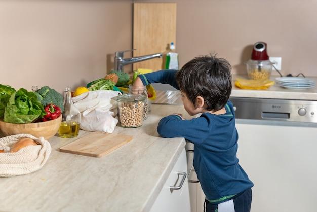 台所のテーブルの上にあるものを見ている小さな好奇心旺盛な少年。ゼロウェイスト。環境にやさしいコットンバッグ