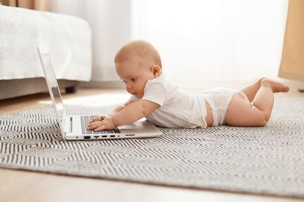 Piccolo bambino curioso che studia la tecnologia moderna mentre è sdraiato sul pavimento sulla pancia contro la finestra, bambino che usa il laptop a casa, bambino che indossa una maglietta bianca.