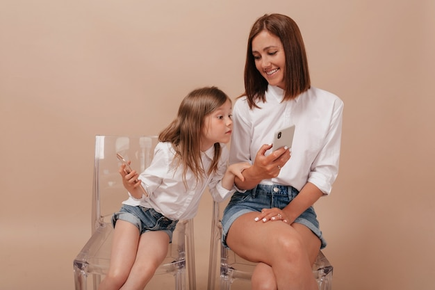 ベージュの背景に面白い母親の携帯電話を探している小さな好奇心旺盛な女の子