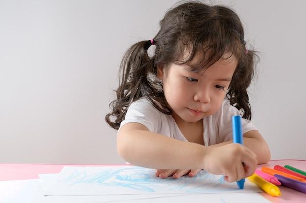 小さな巻き毛のアジアの女の子は、自宅での描画をお楽しみください。教育コンセプト。