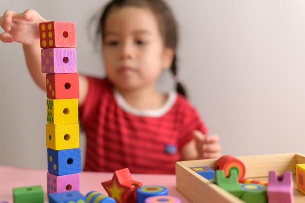 巻き毛のアジアの少女は、白い壁に分離された木のおもちゃブロックで遊んでお楽しみください。教育と学習の概念。