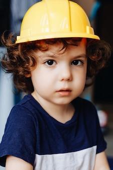 Маленький кудрявый мальчик в строительной каске в своей комнате