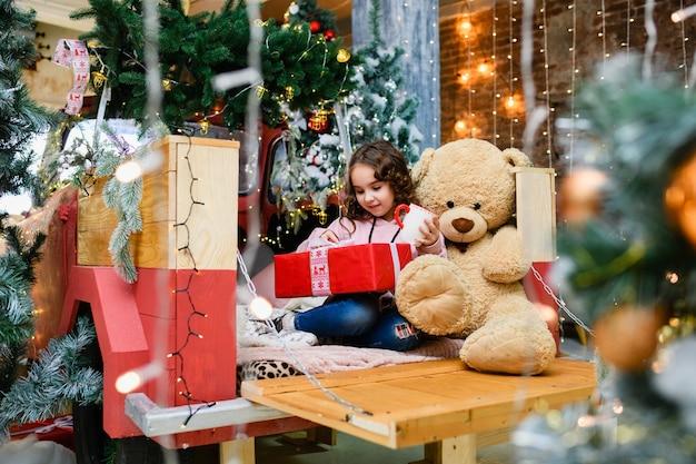 작은 곱슬 갈색 머리 소녀는 크리스마스와 새해 장식 나무 근처에 큰 테디 베어, 컵, 열린 빨간색 선물 상자에 앉아