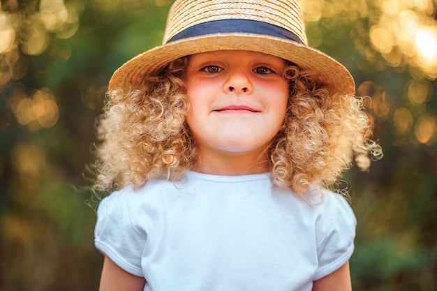 Little curly funny smiling girl in a straw hat.