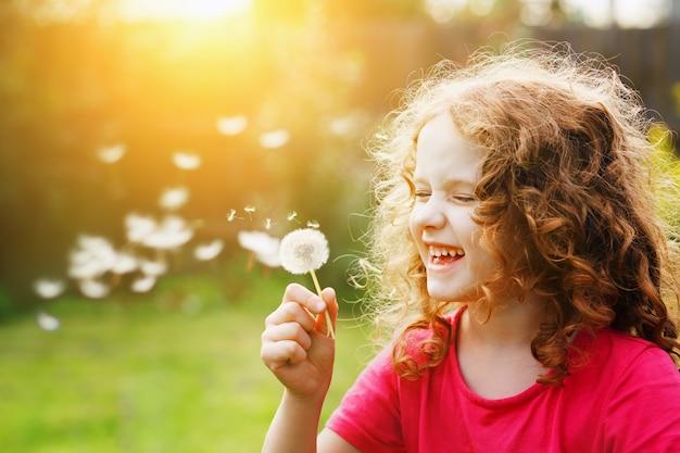Маленькая кудрявая девушка дует одуванчик и смеется.