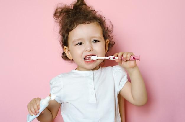 巻き毛の少女が歯磨き粉で歯を磨きます。子供のための個人衛生トレーニング。子供のきれいな口。日常の自宅のバスルームの手順。