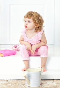 Little curly girl in a pink dress sits with thoughtful look and watch into the distance