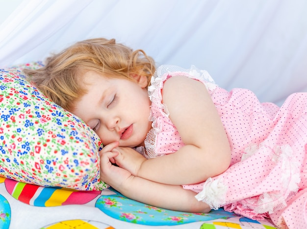 Little curly girl in pink pajamas sleeping with closed eyes on a soft cot