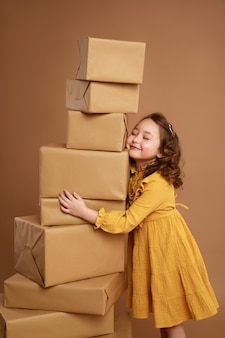 Little curly girl with big stack of gifts for the holiday