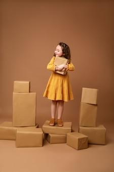 Маленькая кудрявая девочка с большой стопкой подарков к празднику
