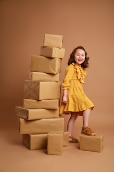 休日の贈り物の大きなスタックを持つ小さな巻き毛の女の子