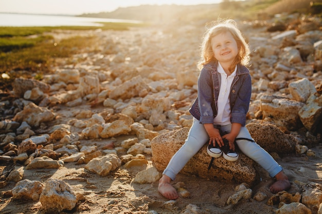 A little curly-haired girl barefoot sits on a rocky beach in summer and holds her shoes in her hands
