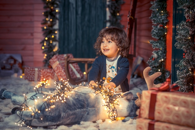 A little curly sweet kid boy in jeans playing with deer toy and christmas lights in the living room on christmas