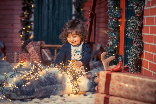 A little curly sweet kid boy in jeans playing with deer toy and christmas lights in the living room