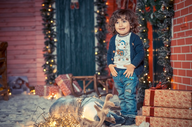 A little curly sweet kid boy in jeans standing near the deer toy and christmas lights in the living room on christmas