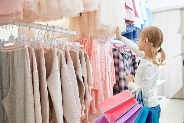 Little customer standing in store and choosing new dresses