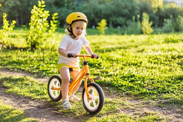 Little cute adorable caucasian toddler girl having fun riding exercise balance run bike push scooter...