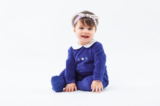Little cute adorable smiling girl with bow in hair sitting in studio posing on white