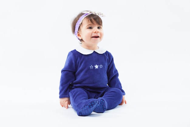 Little cute adorable smiling girl with bow in hair sitting