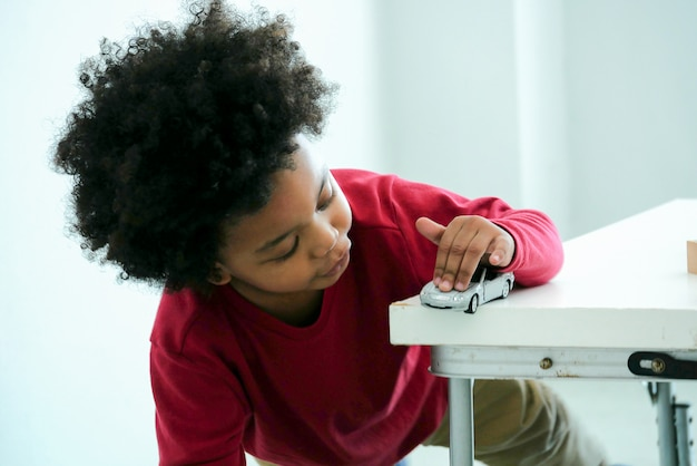 Little cute african boy playing with toy car at home