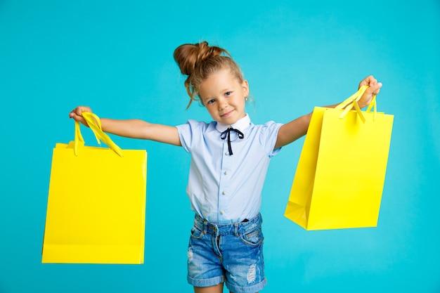 블루 스튜디오에서 큰 밝은 색된 노란색 종이 가방을 들고 작은 귀 엽 고 재미있는 소녀.