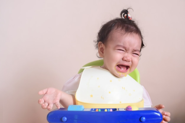 Little cute asian baby girl crying with tearful on her face in dining time, sadness and unhappy, baby expression concept