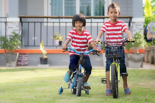 Маленький милый азиатский мальчик и девочка на велосипедах, глядя в камеру, сестра и брат на детской площадке дома