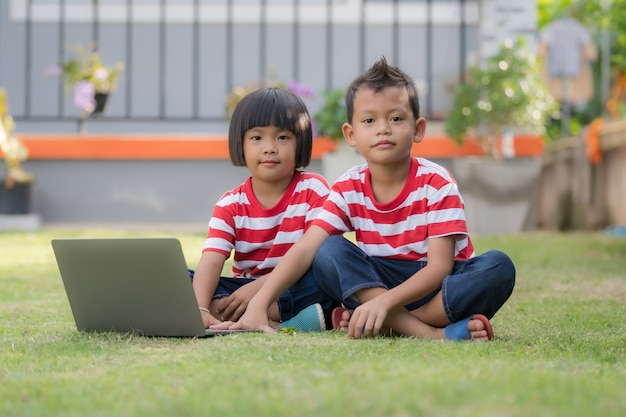 Little cute asian boy and girl using laptop together, looking at camera, watching cartoons or playing online, sister and brother sitting on playground at home