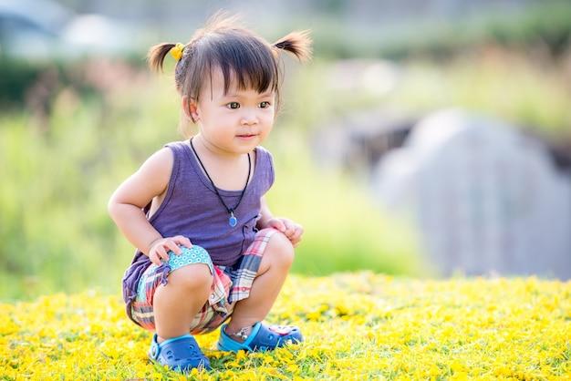 Маленькая милая азиатская девушка в саду
