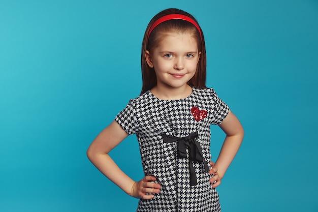 Маленькая милая привлекательная девушка улыбается и держит руки на талии над синей стеной