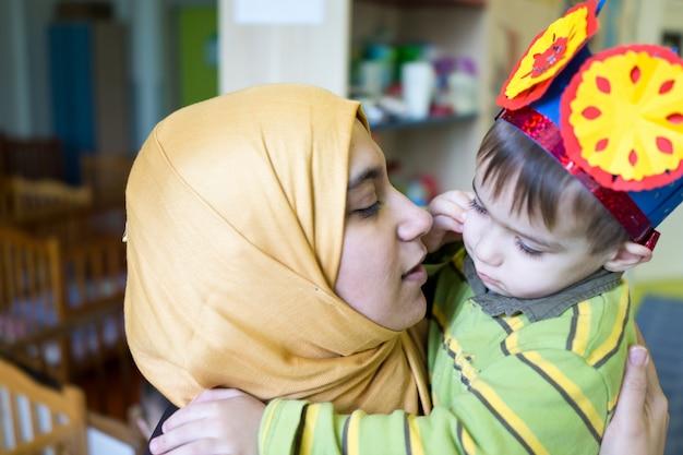 彼の母親を抱きしめてキスする小さなかわいい赤ちゃん少年