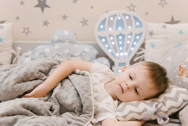 Little cute baby boy lies in the children room in a wooden bed house with night lights in the shape of a balloon, baby falls asleep in the crib