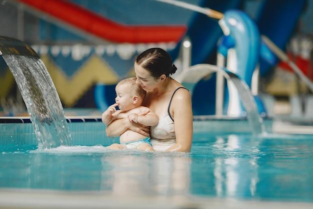 작은 귀여운 아기. 아들과 어머니. 물에서 노는 가족