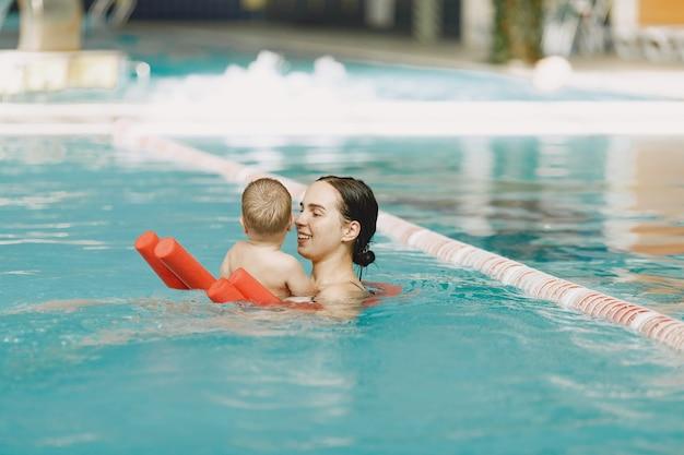 Маленький милый мальчик. мать с сыном. семья играет в воде