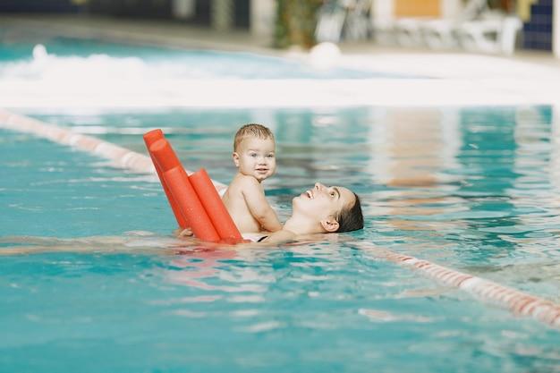 小さなかわいい男の子。息子と母。水で遊ぶ家族