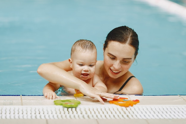 Little cute baby boy. mother with son. family playing in a water
