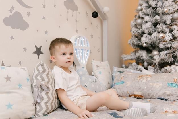 나무 침대에서 어린이 방에 앉아 작은 귀여운 아기