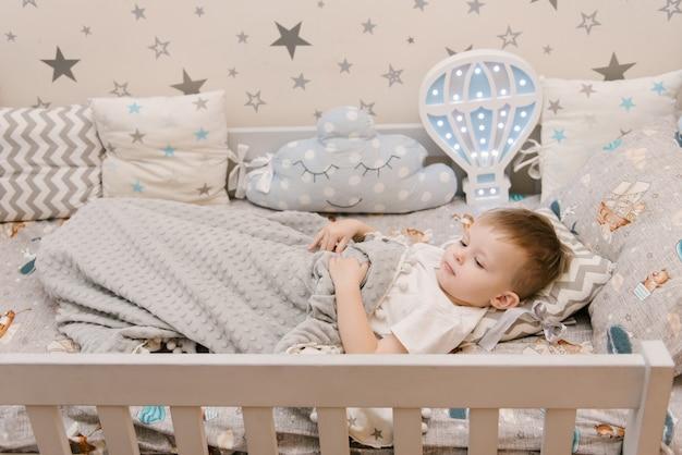 木製のベッドの子供部屋に座っている小さなかわいい男の子