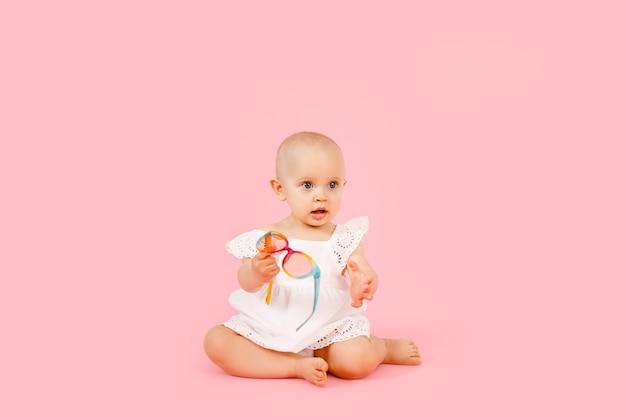 Маленькая милая девочка 1 года в белом летнем платье, изолированном на пастельно-розовом