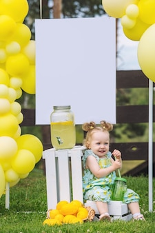 Little cute baby girl beautiful and happy on green grass with balloons and lemonade