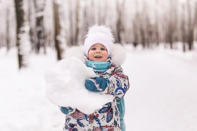 귀여운 아기 소녀는 공원에서 겨울에 큰 눈덩이를 보유
