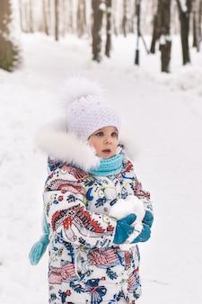 귀여운 아기 소녀는 공원에서 겨울에 눈덩이를 보유