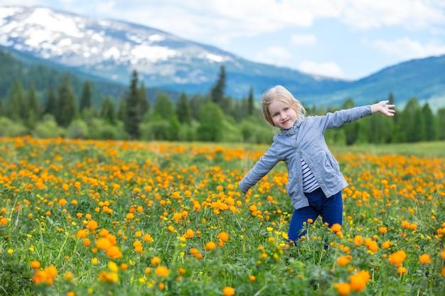 작은 귀여운 아기 소녀는 아름답고 행복하며 눈이 산에 대한 초원에서 여름에 웃고 있습니다.