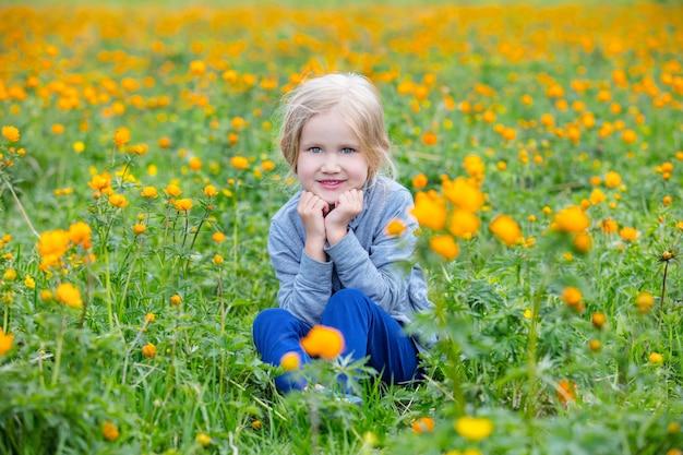小さなかわいい女の赤ちゃんは美しくて幸せで、オレンジ色の花に囲まれた牧草地で夏に笑っています