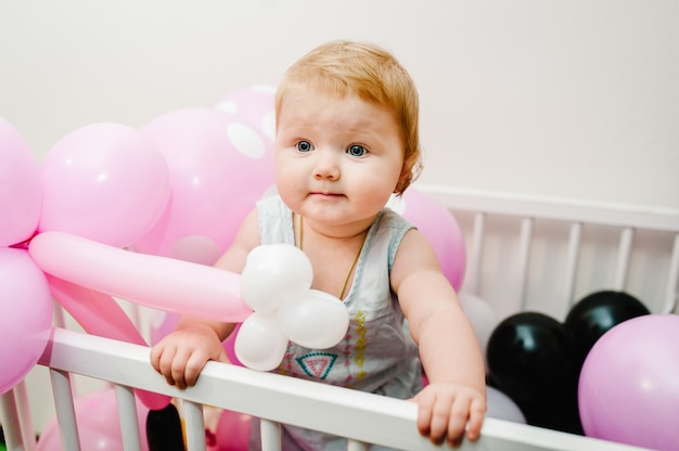 Little cute baby girl princess infant standing and playing on bed