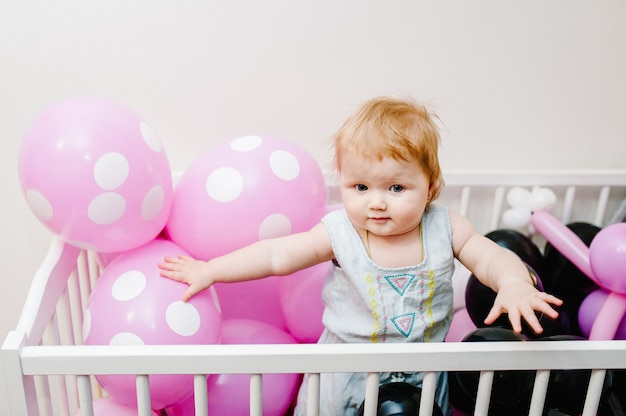 Little cute baby girl princess jumps on a bed and playing with colored air balloons
