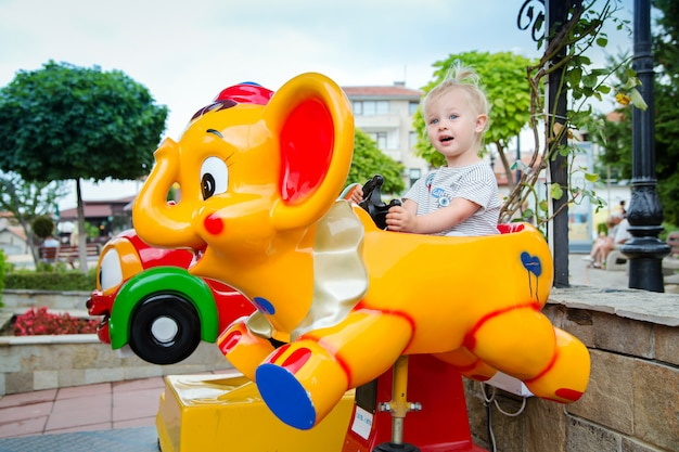 Little cute baby girl riding on the amusement in the park