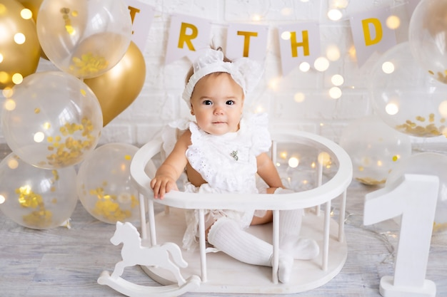 Little cute baby girl sitting with the letters one and balloons, first year, birthday, holiday