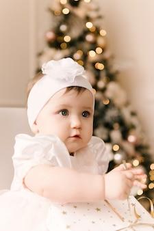 크리스마스 트리 아래 작은 귀여운 아기 소녀. 해피 홀리데이, 새해 복 많이 받으세요. 크리스마스 때