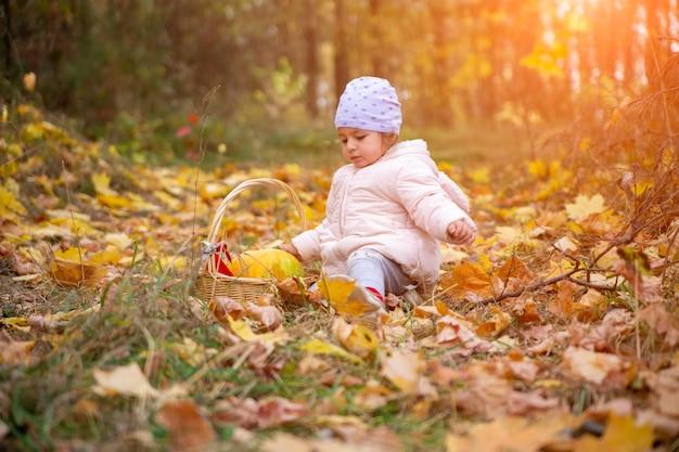 Маленький милый ребенок в куртке в осеннем лесу среди опавших листьев и играет с тыквой